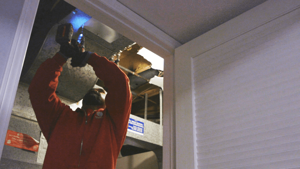 AtlasCare technician working on an air duct