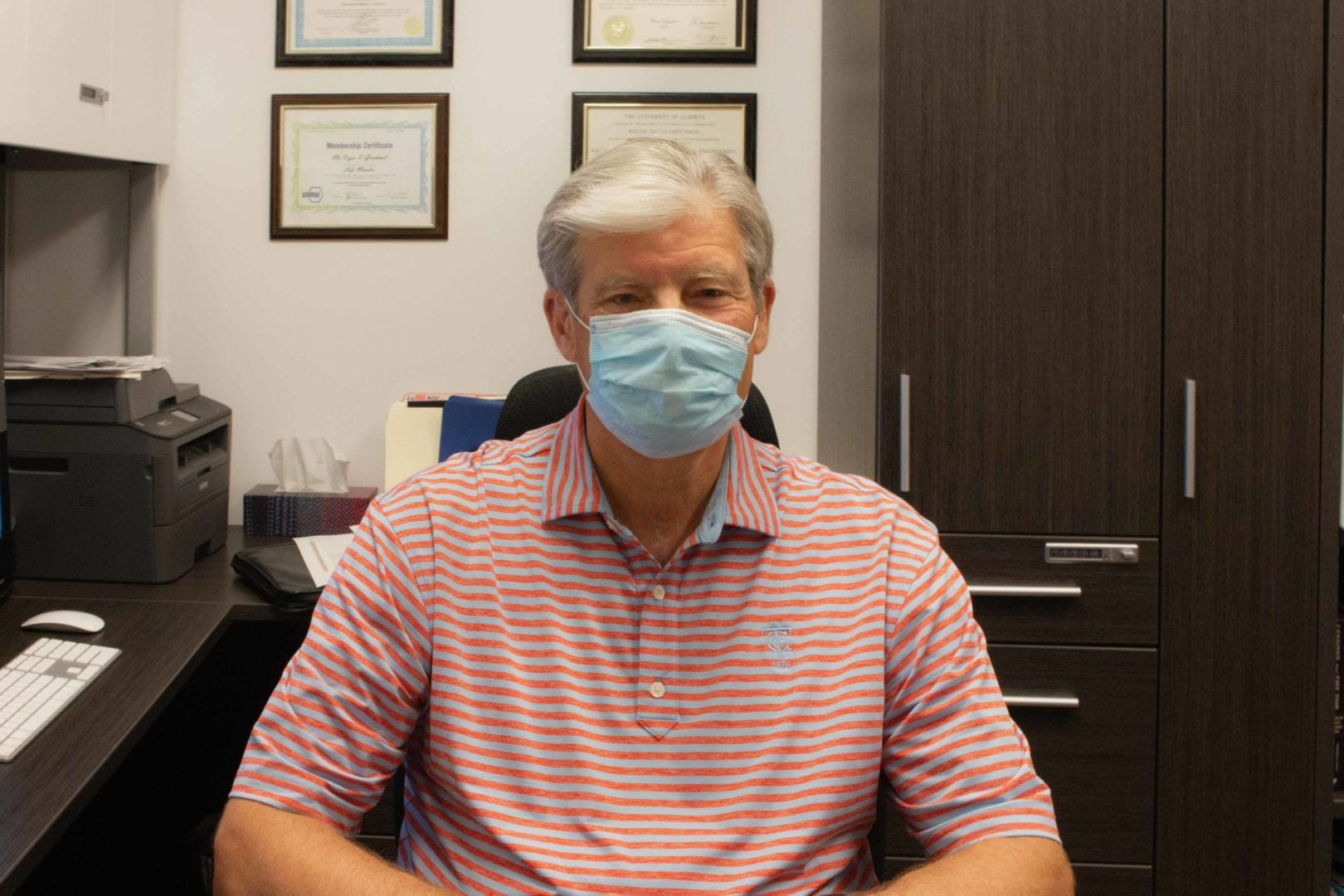 Roger Grochmal sitting in his office wearing a face mask