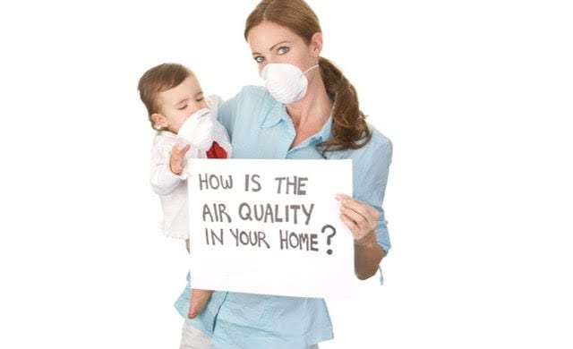 Woman and child wearing a face mask and holding an air quality sign