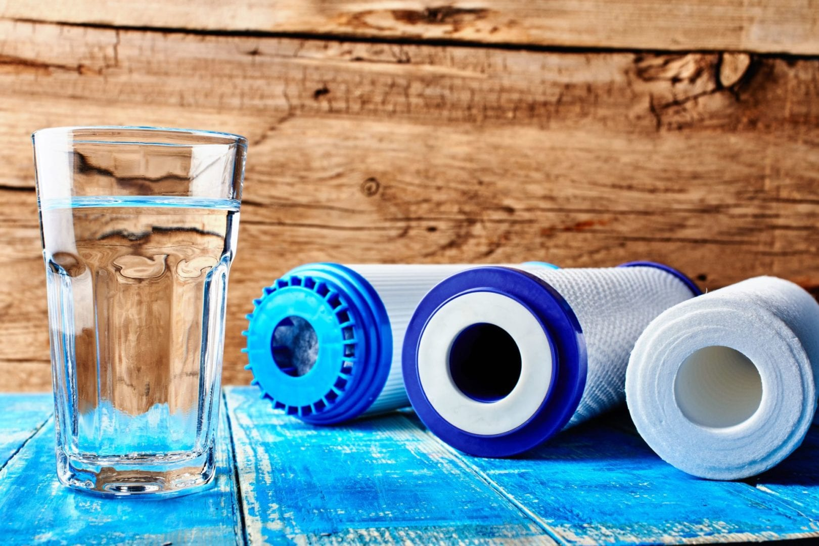 Household water filtration system. Carbon filters and a glass of water on a table.
